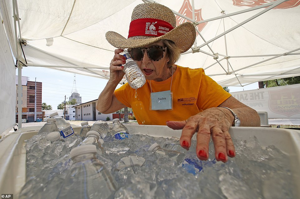 Above Salvation Army volunteer Jackie Rifkin tries to keep cool at she works at a special Salvation Army hydration station to help people try to keep hydrated and stay cool as temperatures climb to near-record highs on Monday in Phoenix