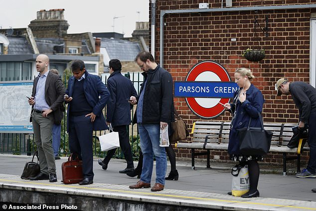 Commuters wait on the platform at Parsons Green station in London, Monday, Sept. 18, 2017. A bucket wrapped in an insulated bag caught fire on a packed London subway train at Parsons Green station on Friday Sept. 15, police are treating it as a terrorist incident. (AP Photo/Kirsty Wigglesworth)