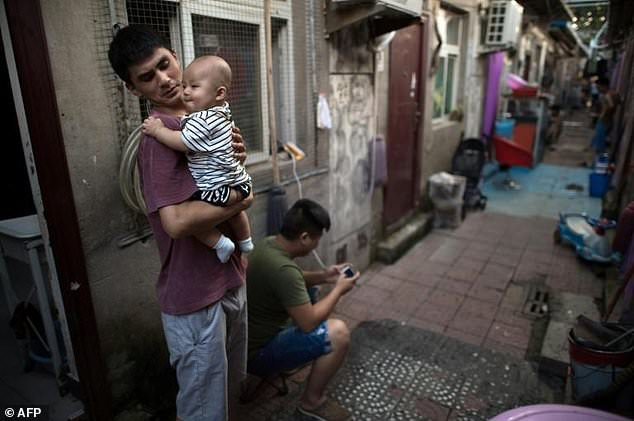 A man holds his baby outside his room in a migrant village on the outskirts of Beijing