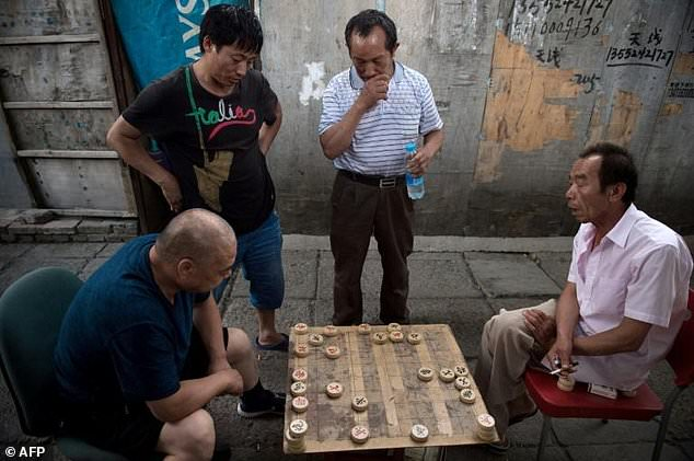 People play Chinese chess on a street in a migrant village on the outskirts of Beijing