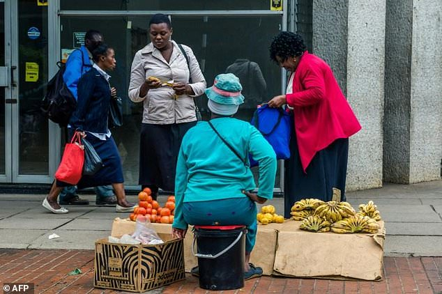 Residents buy fruits from a street vendor in Harare on November 15, 2017. Zimbabwe's military appeared to be in control of the country though generals denied staging a coup