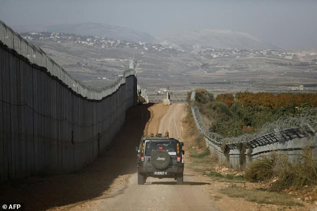 An Israeli army vehicle drives along the border fence between Lebanon and Israel near the northern Israeli town of Metula on November 16, 2017