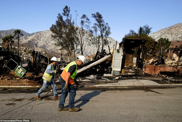 Workers from the Los Angeles Department of Water and Power walk past a home destroyed by the Creek Fire along Via San Anselmo in the Sylmar area of Los Angeles