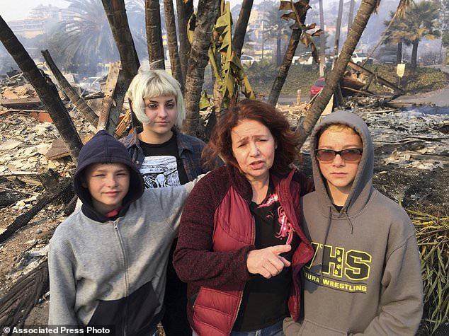 "Lisa Kermode, second from right, and her children, from left, Damien, Lola and Michael, pose outside the ruins of their home after a wildfire swept through Ventura, Calif., Tuesday, Dec. 5, 2017. They were home Monday night when Lisa started to smell smoke and her phone buzzed with an alert, urging residents to evacuate. ""Within an hour, it was here,"" she said. ""We left. We grabbed nothing,"" she said Tuesday. ""We lost everything."" (AP Photo/Amanda Lee Myers)"