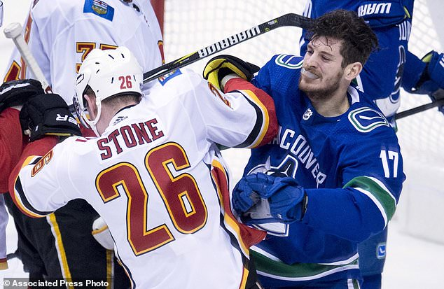 Vancouver Canucks center Nic Dowd (17) pushes Calgary Flames defenseman Michael Stone (26) during second period NHL hockey action in Vancouver, British Columbia, Sunday, Dec. 17, 2017. (Jonathan Hayward/The Canadian Press via AP)