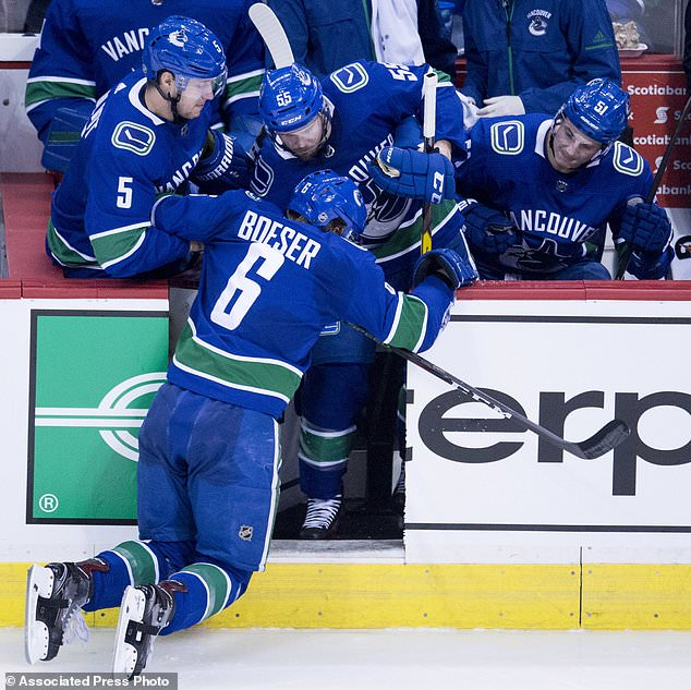Vancouver Canucks defenseman Derrick Pouliot (5), defenseman Alex Biega (55) and defenseman Troy Stecher (51) help right wing Brock Boeser (6) off the ice after taking a hit during second period NHL hockey action against the Calgary Flames in Vancouver, British Columbia, Sunday, Dec. 17, 2017. (Jonathan Hayward/The Canadian Press via AP)