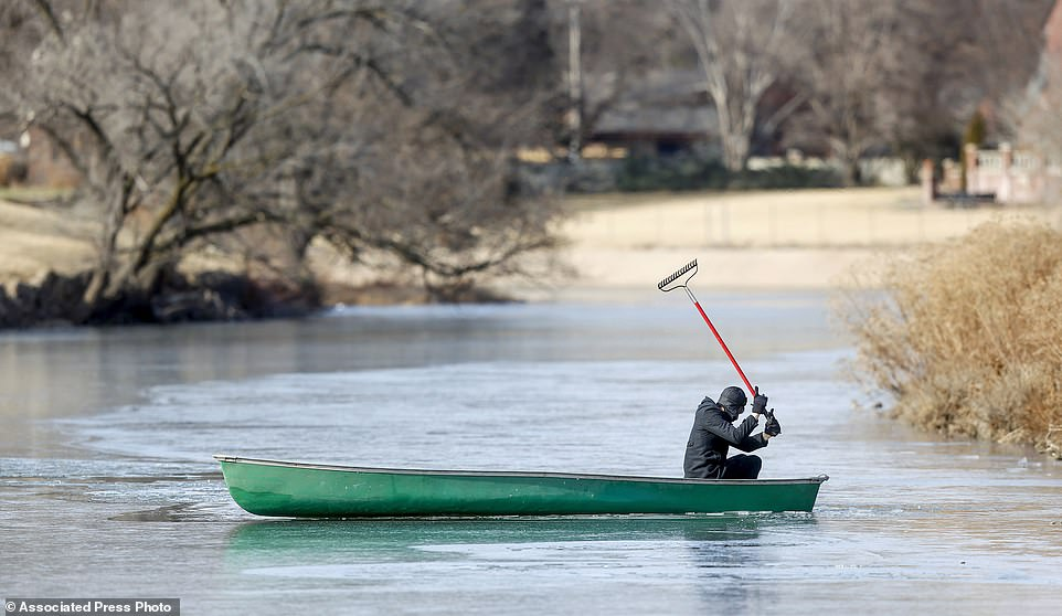 Tim Christmore uses a rake to get his canoe through the ice-covered Little Arkansas River in Wichita, Kansas on Tuesday