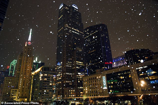 Public safety authorities, including Austin Police Chief Brian Manley, are asking residents to avoid driving unless it's an emergency (Pictured, snow and sleet falls in Downtown Dallas on Monday evening)