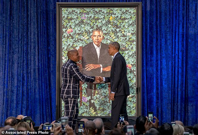 Former President Barack Obama, right, and Artist Kehinde Wiley, left, shake hands as they unveil Obama's official portrait at the Smithsonian's National Portrait Gallery, Monday, Feb. 12, 2018, in Washington. (AP Photo/Andrew Harnik)