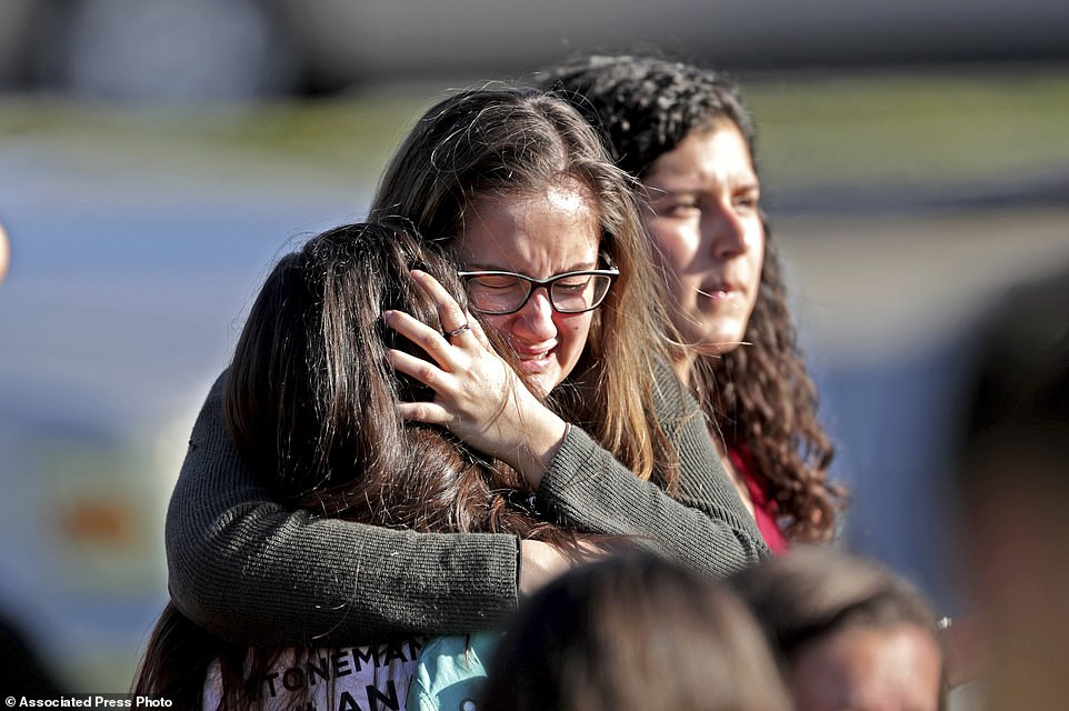 Students released from a lockdown embrace following following a shooting at Marjory Stoneman Douglas High School in Parkland, Fla., Wednesday, Feb. 14, 2018. (John McCall/South Florida Sun-Sentinel via AP)