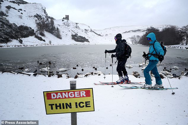 David Webb (left) and his wife Louise Bath, from Edinburgh, ski around St Margaret´s Loch in Holyrood Park (Jane Barlow/PA)