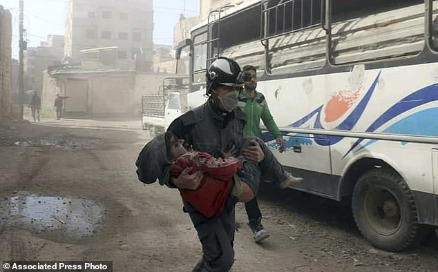 A member of the Syrian Civil Defense group carrying a boy who was wounded during airstrikes and shelling by Syrian government forces in Ghouta, a suburb of Damascus, on Friday