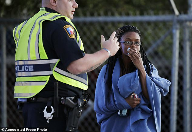 An employee wrapped in a blanket talks to a police officer after she was evacuated at a FedEx distribution center where a package exploded, Tuesday, March 20, 2018, in Schertz, Texas. Authorities believe the package bomb is linked to the recent string of Austin bombings. (AP Photo/Eric Gay)