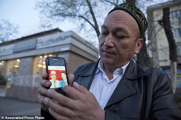 Omir Bekali holds up a mobile phone showing a photo of his parents whom he believes have been detained in China, in Almaty, Kazakhstan