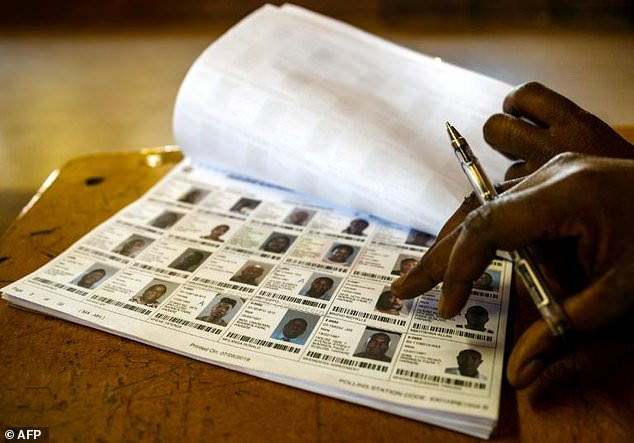 A Zimbabwe Electoral Commissioon (ZEC) official checks names in the voter roll register which critics say has been padded out with babies, the dead and bogus names in the past to help rig elections