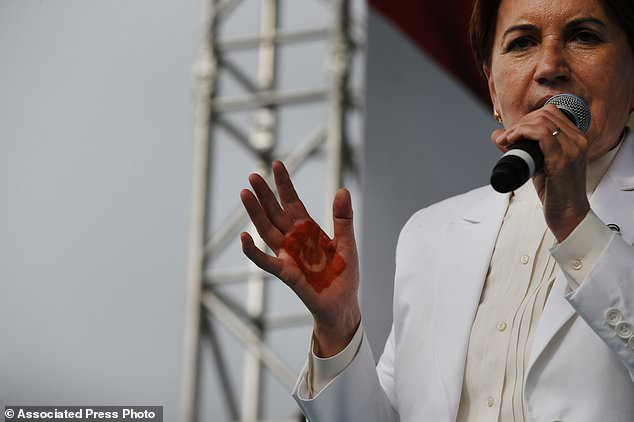 In this Tuesday, June 19, 2018 photo, Meral Aksener, 61, the presidential candidate of nationalist opposition IYI (Good) Party, with a Turkish flag painted on her palm, talks during an election rally, ahead of the June 24 elections, in Kocaeli, Turkey. Turkey's President Recep Tayyip Erdogan is facing a tough challenge to his 15 years in power from a more united and galvanised opposition in snap presidential and parliamentary elections, trying to thwart his attempt to remain in office with vastly increased powers. (AP Photo/Lefteris Pitarakis)