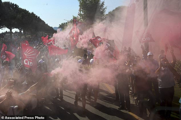 In this Tuesday, June 13, 2018 photo, supporters of Muharrem Ince, presidential candidate of Turkey's main opposition Republican People's Party, wave flags and hold flares as he arrives for an election rally in Mugla, Turkey. The combative 54-year-old former physics teacher is seen as a strong contender to end Turkey's President Recep Tayyip Erdogan's 16 year rule. (Ziya Koseoglu/CHP Press Service via AP, Pool)