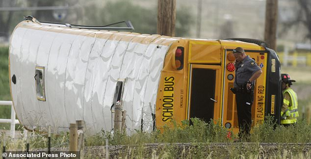 A Weld County Sheriffs Deputy talks on the phone at the scene of a crash involving a school bus on Thursday