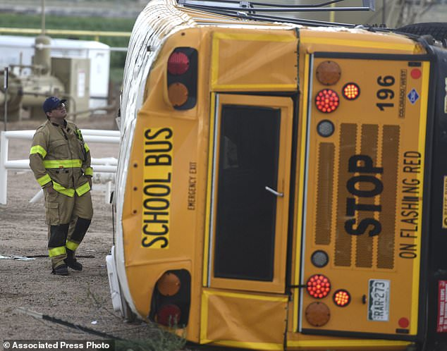 A firefighter investigates the wreckage of a school bus after it flipped near the intersection of Weld County Road 49 and Weld County Road 24 near Hudson, Colorado