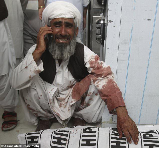 Un homme parle sur un téléphone assis à côté d'un membre de sa famille tué dans un attentat à la bombe, à Quetta, au Pakistan, vendredi 13 juillet 2018. Soulignant la menace à la sécurité, deux bombes ont explosé vendredi la violence à frapper le Pakistan. La première bombe qui a tué quatre personnes a explosé dans le nord-ouest du Pakistan près du rassemblement électoral d'un haut responsable politique d'un parti islamiste qui se présente au parlement de la ville de Bannu, au nord-ouest du pays. (Photo AP / Arshad Butt)
