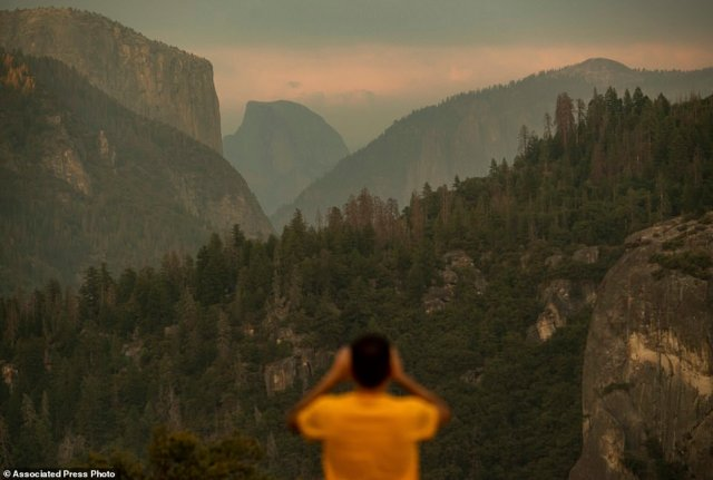 Francisco Avendano, visiting from Madrid, Spain, photographs Half Dome as smoke from the Ferguson Fire hangs over Yosemite National Park