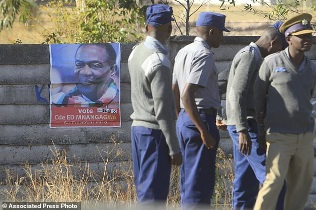 Zimbabwe police officers stand next to a campaign poster of Zimbabwean President Emmerson Mnangagwa at Nelson Chamisa's rally in Chitungwiza about 30 kilometres east of the capital Harare, Thursday, July, 26, 2018. Chamisa addressed his first rally since rejecting the idea of boycotting elections on Monday despite what he calls a biased election commission, in the first election since the November resignation of longtime leader Robert Mugabe. (AP Photo/Tsvangirayi Mukwazhi)