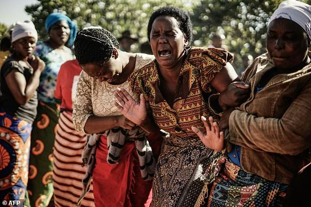 Suspicious Ziyambi, widow of Ishmael Kumire, 42, weeps during her husband's funeral ceremony