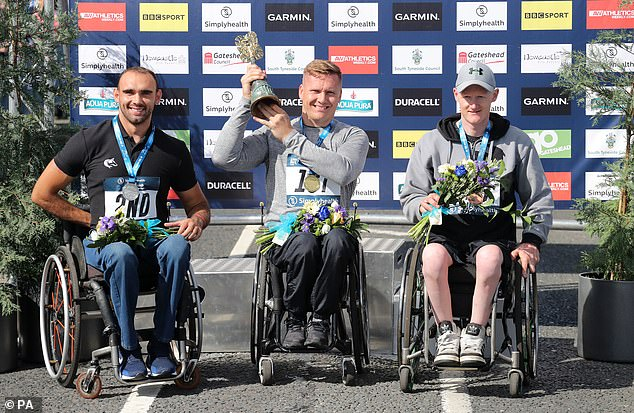 Weir (centre) celebrates after winning the Great North Run elite wheelchair race on Sunday