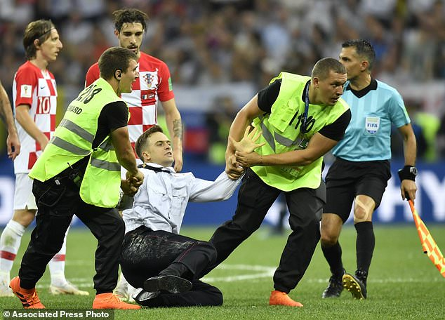 FILE - This July 15, 2018, stewards Pyotr Verzilov, a member of the feminist protest group Pussy Riot, pull away from the field after being stormed to the field and interrupted the final between France and Croatia at the 2018 FIFA World Cup in Luzhniki Stadium in Moscow, Russia. Russian news reports that Verzilov, a member of Russian punk protest group Pussy Riot, was hospitalized for serious poisoning. (AP photo / Martin Meissner, file)