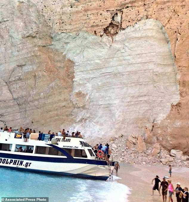 People embark a ship after a landslide occurred at the popular beach of Navagio, or Shipwreck Beach, on the western island of Zakynthos, Greece, Thursday, September 13, 2018. Greek authorities say a landslide on a popular beach on the western island of Zakynthos has resulted in at least one injury while the Coast Guard was trying to find out if any were missing. (imerazante.gr via AP)