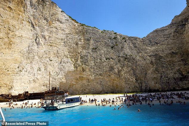 FILE - This Friday, September 8, 2017 file photo, people enjoy the popular beach of Navagio, or Shipwreck Beach, on the western island of Zakynthos, Greece. The Greek authorities reported on Thursday, September 13, 2018, that a landslide on a popular beach on the western island of Zakynthos caused at least one injury while the Coast Guards attempted to find out if people were missing. (AP Photo / Petros Karadjias, file)