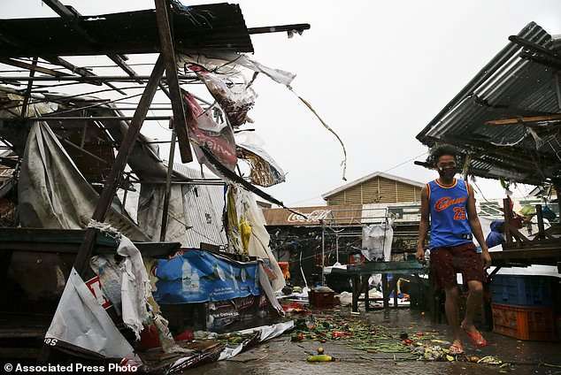 A resident walks along destroyed stalls at a public market due to strong winds as Typhoon Mangkhut barreled across Tuguegrao city in Cagayan province, northeastern Philippines on Saturday, Sept. 15, 2018. The typhoon slammed into the Philippines northeastern coast early Saturday, it's ferocious winds and blinding rain ripping off tin roof sheets and knocking out power, and plowed through the agricultural region at the start of the onslaught. (AP Photo/Aaron Favila)