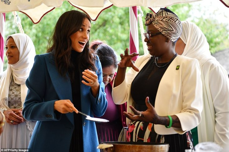Meghan talks to one of the cooks as she helps to prepare food at the launch of the book, with recipes from a group of women