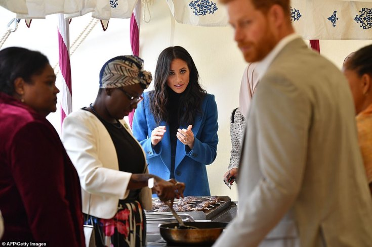Harry watches on as the Duchess helps to prepare food at the launch of the cookbook in Kensington Palace