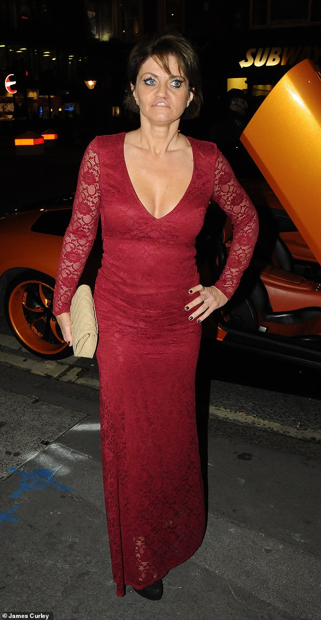 Work it: Danniella Westbrook, 44, was in the mood to dazzle as she slipped her figure into a perilously plunging wine-coloured gown