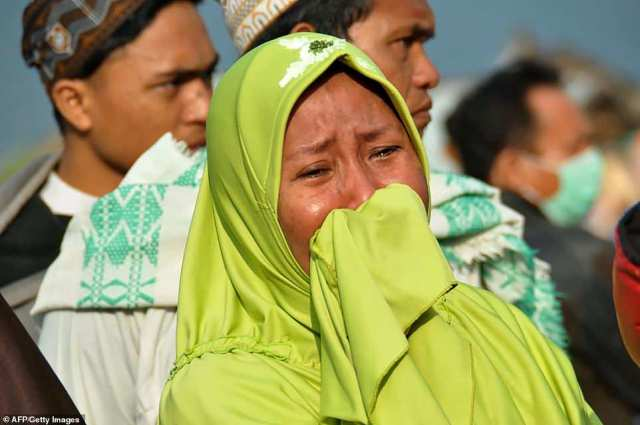 A woman cries as people begin to realise the extent of the damage and the number of casualties after an earthquake and a tsunami hit Palu.Thousands of buildings have been damaged, with some entirely swept away or demolished, leaving scores of families missing among the debris