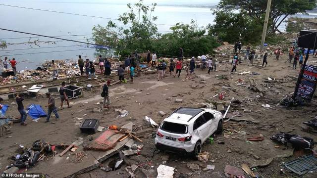 Many of those killed in Palu were swept away by giant waves more than 10ft high as they played on the beach in the scenic tourist town. The National Disaster Mitigation Agency warned early on of reports showing that 'victims died in the rubble of a collapsed building'