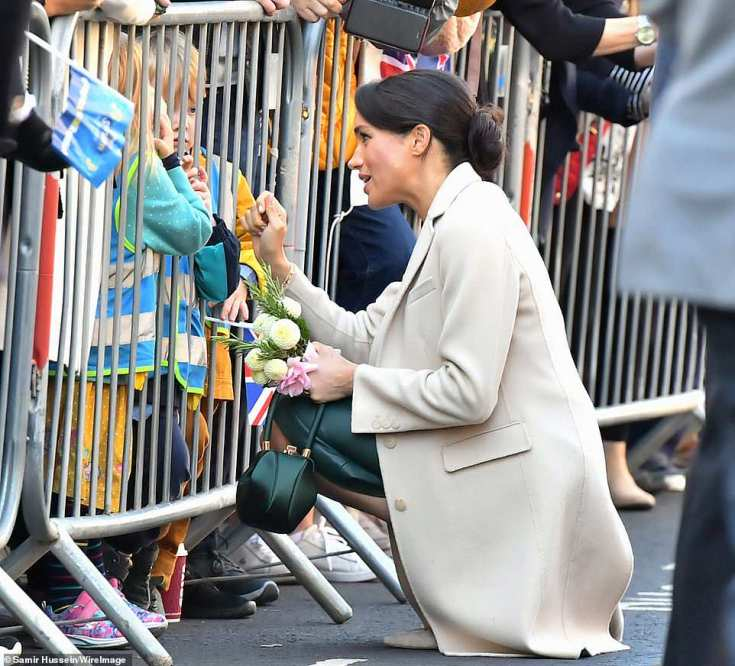 The Duchess of Sussex speaks to two young children behind a barrier as she arrives in Chichester this morning