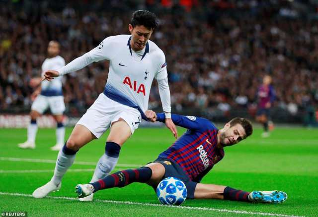 Son Heung-min tries to get around Barcelona's veteran defender Gerard Pique but he grabs hold of his shirt to contain him