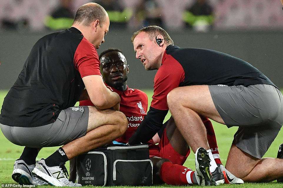 Liverpool midfielder Naby Keita is attended to by Liverpool's medical team after suffering a leg injury during the first half