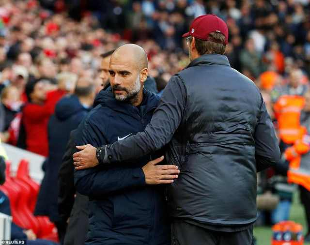 The two managers hug before the game as Pep Guardiola (left) looks to break his Anfield hoodoo on Sunday afternoon
