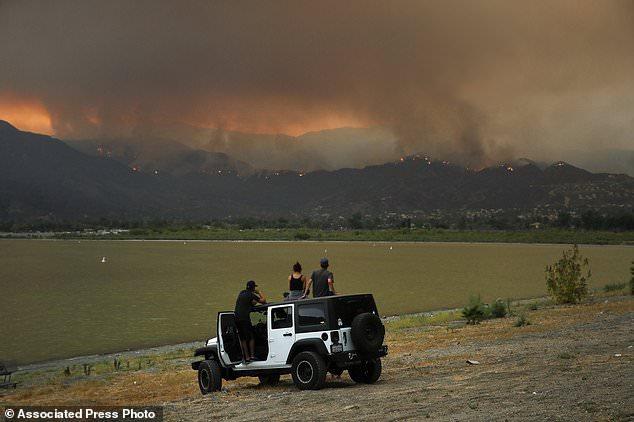 Zuschauer beobachten wie ein Lauffeuer in der Nähe von Lake Elsinore, Kalifornien, Mittwoch, 8. August 2018. Evakuierungen wurden für mehrere kleine Berggemeinden in der Nähe, wo ein Waldbrand in Südkalifornien wächst weiter bestellt. (AP Foto / Jae C. Hong)