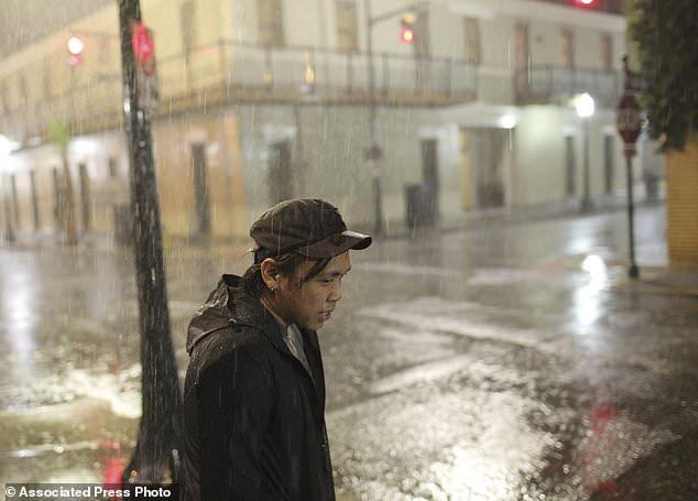 Charles Phanthapannha steht im Regen vor einer Bar, als Tropical Storm Gordon am Dienstag, 4. September 2018, in Mobile, Ala anreist. Tropische Sturmwinde vom schnell fahrenden Gordon brechen am Dienstagabend in die Küstenlinie von Alabama und dem westlichen Florida Panhandle , die Frontalkante eines Systems direkt vor der Küste, das von den Meteorologen gewarnt wurde, könnte zu einem Hurrikan werden, wenn es auf Land trifft. (AP Foto / Dan Anderson)
