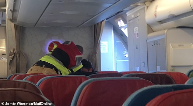 Dramatic: The man was brought onto the plane from the back and was seated with Home Office staff on either side of him