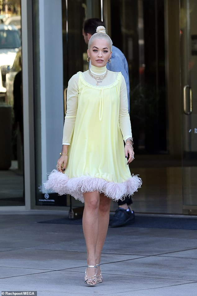 Incredible: The singer looked absolutely sensational as she showed off her toned legs in a yellow shift dress with a feathered hem