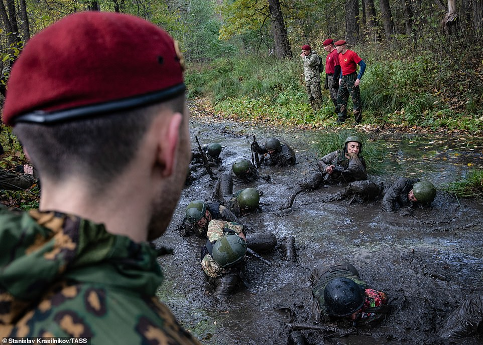 Soldiers who have already earned their maroon berets watch as the hopefuls crawl through a muddy swamp