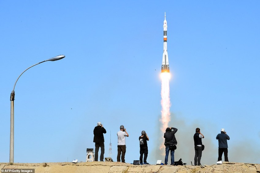 Photographers take pictures as Russia's Soyuz MS-10 spacecraft jets into the sky during its launch in Kazakhstan on Thursday. The world's media had gathered for the launch at theBaikonur Cosmodrome to herald the beginning of a joint project between the Russian and American space agencies