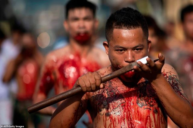 Gory: Other devotees paraded down the street while cutting themselves, covered in their own blood