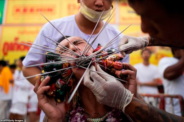 Pierced: A man winces in pain as more than a dozen skewers are inserted through his cheeks