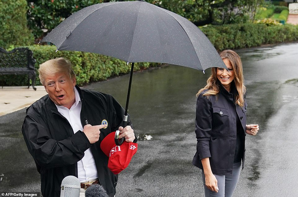 Fending for herself: While her husband held an umbrella, Melania was at times left to stand in the rain as he mainly used it for himself while talking to the media